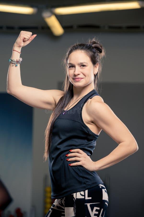 Het brunette toont haar atletische bicepsen stock fotografie