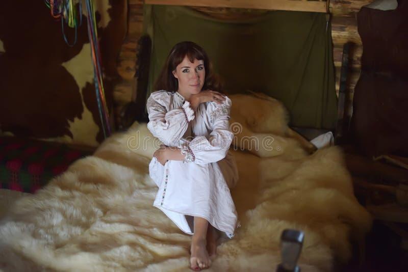Het brunette in wit linnen ouderwets overhemd met borduurwerk zit op een middeleeuws bed royalty-vrije stock foto's