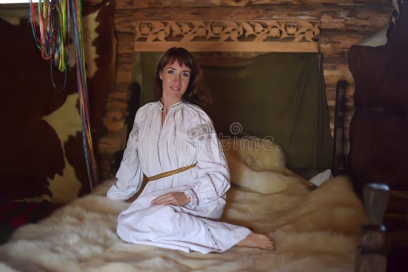 Het brunette in wit linnen ouderwets overhemd met borduurwerk zit op een middeleeuws bed royalty-vrije stock afbeeldingen