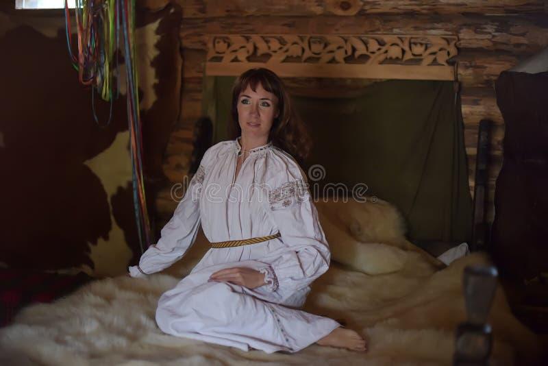 Het brunette in wit linnen ouderwets overhemd met borduurwerk zit op een middeleeuws bed stock fotografie