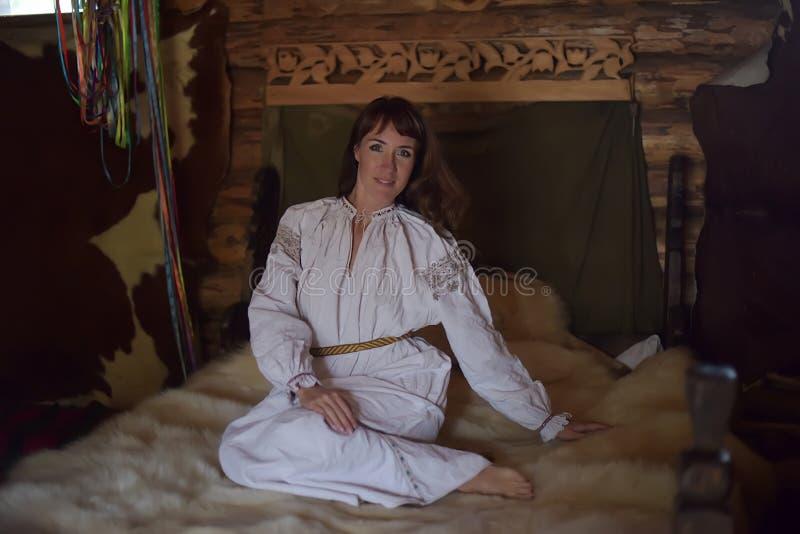 Het brunette in wit linnen ouderwets overhemd met borduurwerk zit op een middeleeuws bed stock afbeeldingen