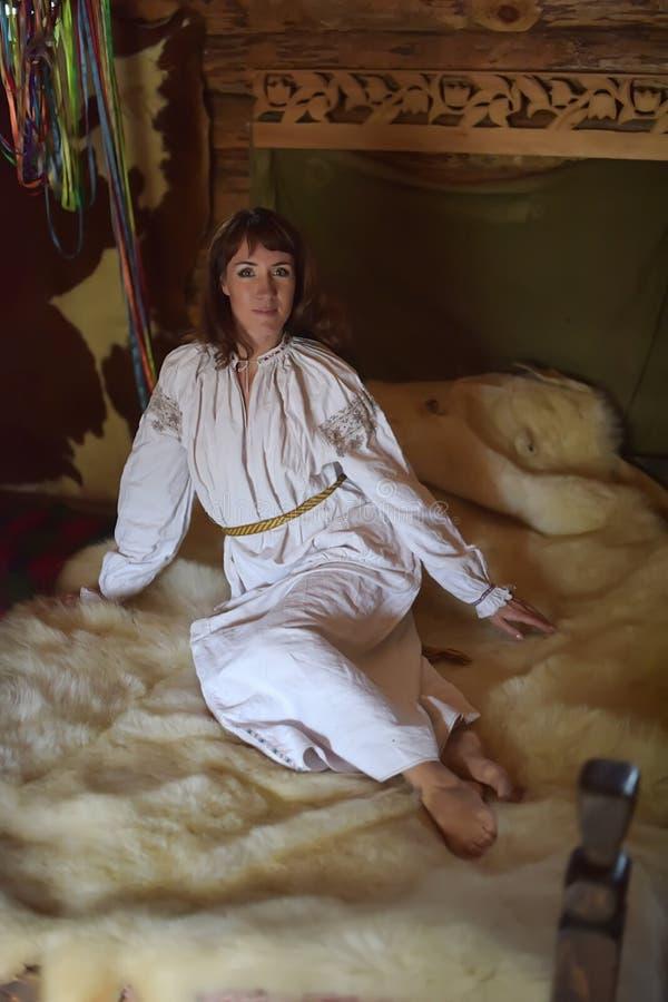 Het brunette in wit linnen ouderwets overhemd met borduurwerk zit op een middeleeuws bed stock foto