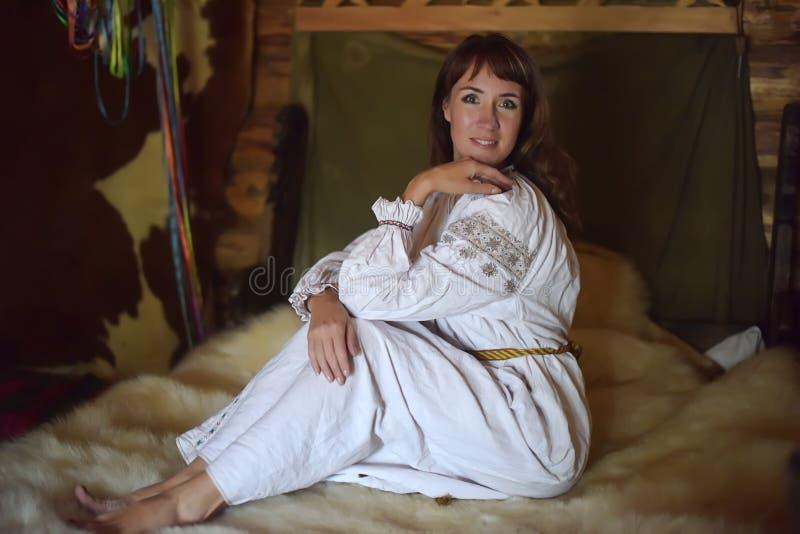 Het brunette in wit linnen ouderwets overhemd met borduurwerk zit op een middeleeuws bed stock foto's