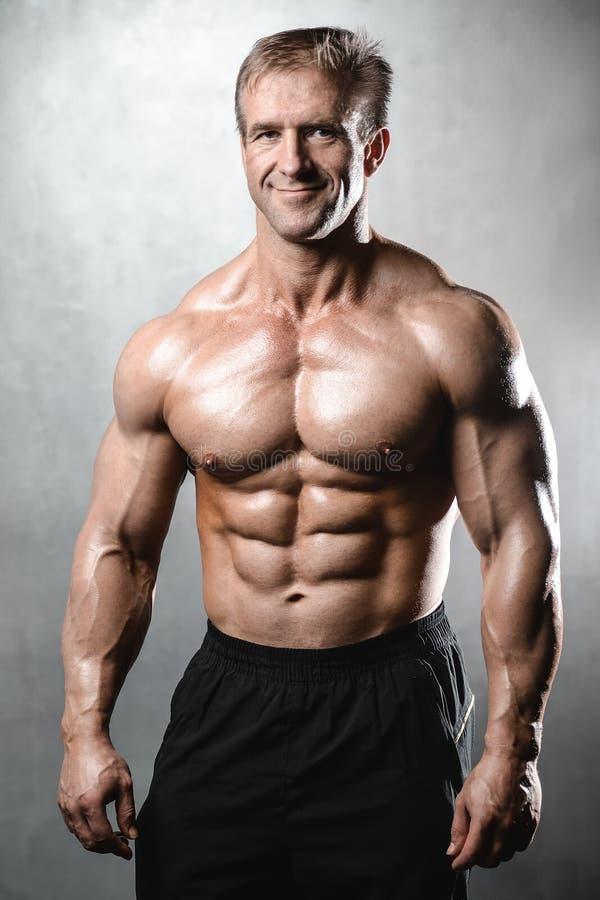 Het brutale sterke bodybuilder oude mens stellen in studio grijze backgrou royalty-vrije stock foto's
