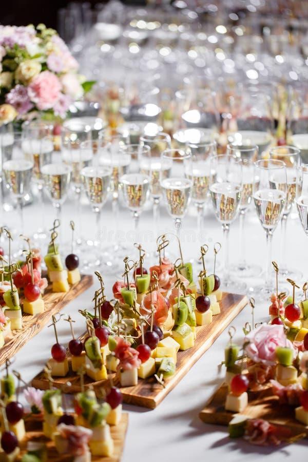 Het buffet bij de ontvangst Glazen wijn en champagne Assortiment van canapes op houten raad De banketdienst royalty-vrije stock foto's