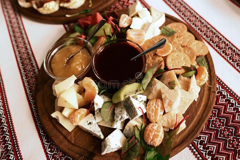Het buffet met een plaat van voorgerechten van verschillende verscheidenheden van kaas, vruchten, sausen, crackers, borduurde doe stock afbeeldingen