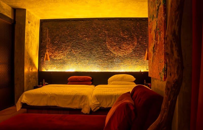 Het buitengewoon brede bed van de koningsgrootte in decoratieve humeurige ruimte met de muur van de douanehoofdsteun stock foto's