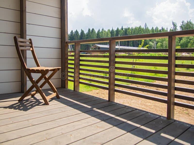 Het buitenhuisterras, hotel, tuiniert houten meubilair, een stoel Op de achtergrond is een groen gazon Horizontale richtlijn, rui stock foto's