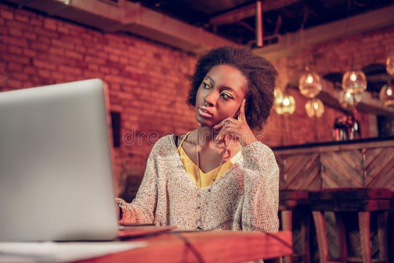 Het buitensporige vrouwelijke denken over nieuw project amid het zitten bij laptop stock foto's