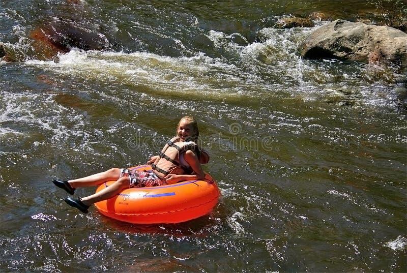 Het buizenstelsel van het tienermeisje onderaan een rivier stock foto's