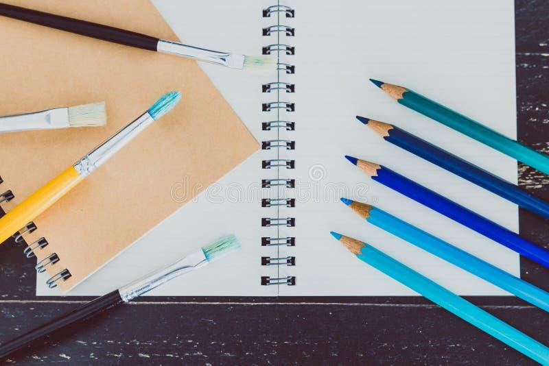 Het bureau met blocnotes en watercolour borstelt en gekleurde potloden met lege pagina's en copyspace royalty-vrije stock foto