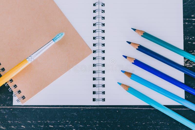 Het bureau met blocnotes en watercolour borstelt en gekleurde potloden met lege pagina's en copyspace stock afbeeldingen