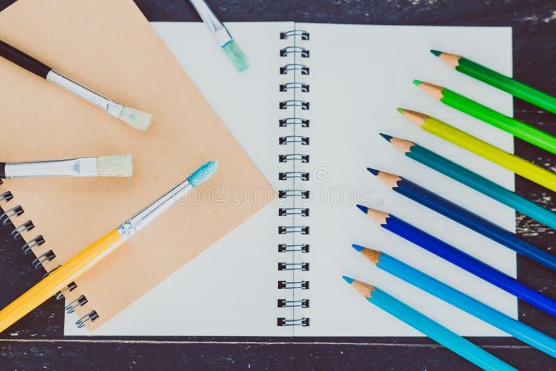 Het bureau met blocnotes en watercolour borstelt en gekleurde potloden met lege pagina's en copyspace royalty-vrije stock foto's