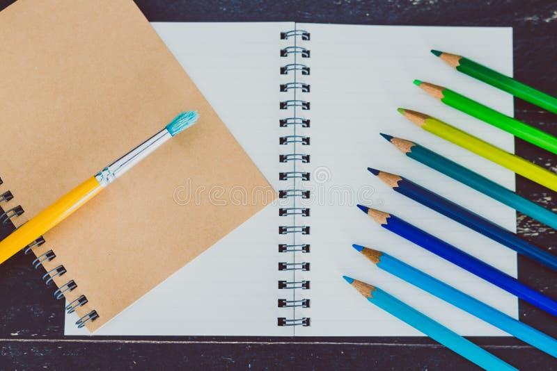 Het bureau met blocnotes en watercolour borstelt en gekleurde potloden met lege pagina's en copyspace stock foto's