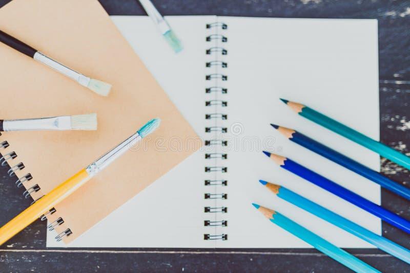 Het bureau met blocnotes en watercolour borstelt en gekleurde potloden met lege pagina's en copyspace stock foto