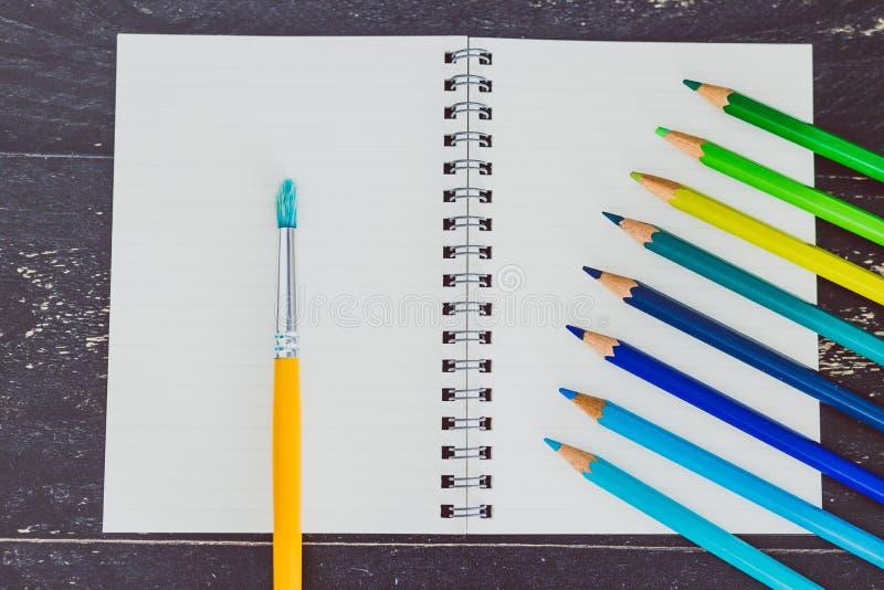Het bureau met blocnotes en watercolour borstelt en gekleurde potloden met lege pagina's en copyspace stock afbeelding