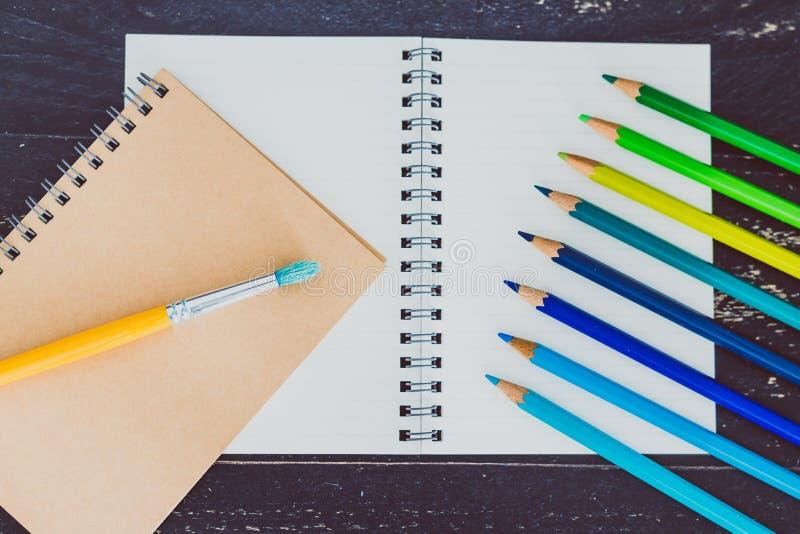 Het bureau met blocnotes en watercolour borstelt en gekleurde potloden met lege pagina's en copyspace royalty-vrije stock afbeeldingen