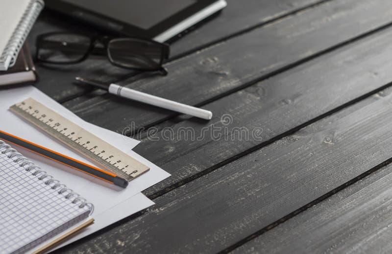Het bureau met zaken heeft - open notitieboekje, tabletcomputer, glazen, heerser, potlood, pen bezwaar De werkplaats van het bure royalty-vrije stock afbeelding