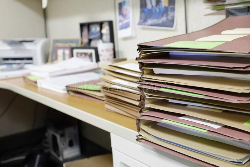 Het bureau stapelde zich omhoog met Dossiers en het Werk op stock foto