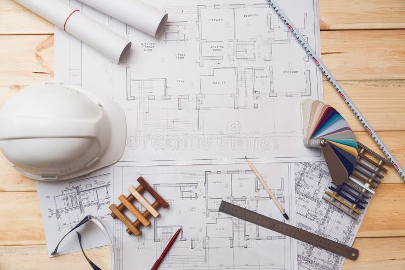 Het bureau van de architectuurtekening, bouwwerf die met blauwdrukken in de bureau hoogste mening werken stock foto