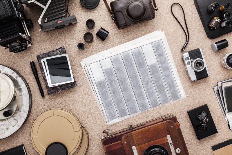 Het bureau van de fotograaf De uitstekende camera's, verbiedt en rolt van film Vlak leg stock fotografie
