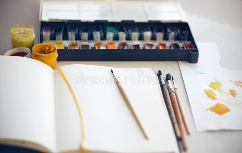 Het Bureau van de kunstenaar waarop sketchbook, borstels, waterverf en gouacheverven stock foto