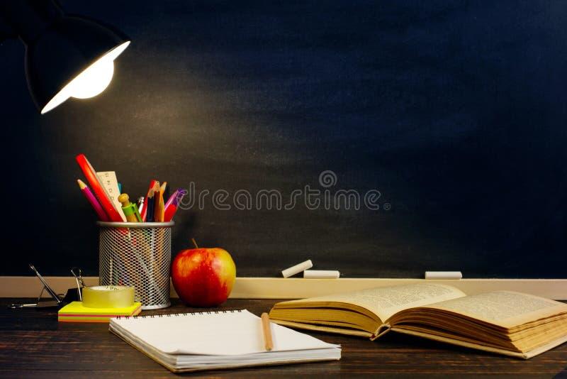 Het bureau van de leraar of een arbeider, waarop het schrijfgerei, een boek en een appel, in de avond onder de lamp ligt Spatie v stock foto's