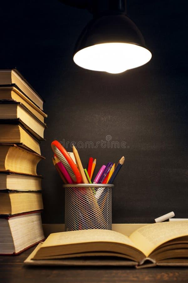 Het bureau van de leraar of een arbeider, waarop het schrijfgerei ligt, boeken, in de avond onder de lamp Spatie voor tekst of stock fotografie