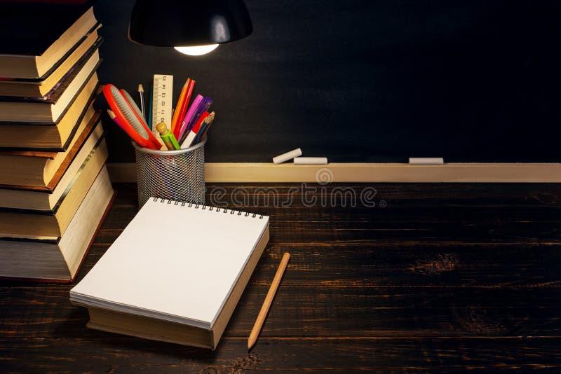 Het bureau van de leraar of een arbeider, waarop het schrijfgerei ligt, boeken, in de avond onder de lamp Spatie voor tekst of stock afbeeldingen
