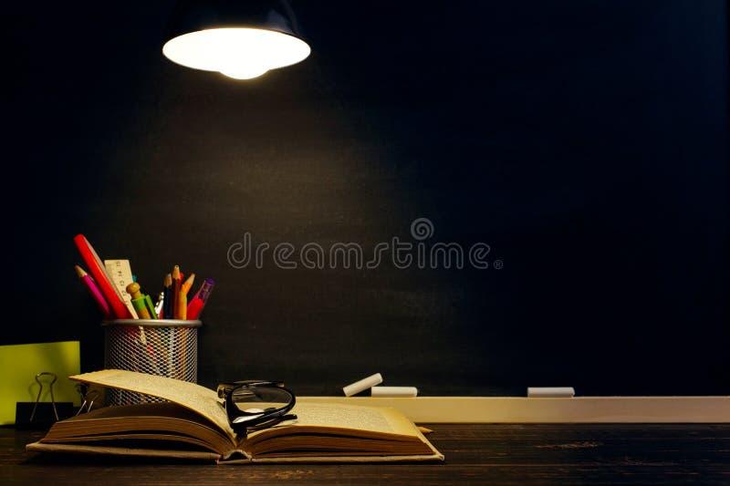 Het bureau van de leraar of een arbeider, waarop het schrijfgerei ligt, boeken, in de avond onder de lamp Spatie voor tekst of stock foto's