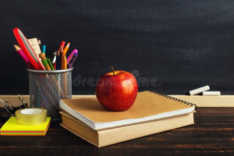 Het bureau van de leraar met schrijfgerei, een boek en een appel, een spatie voor tekst of een achtergrond voor een school als th stock afbeeldingen