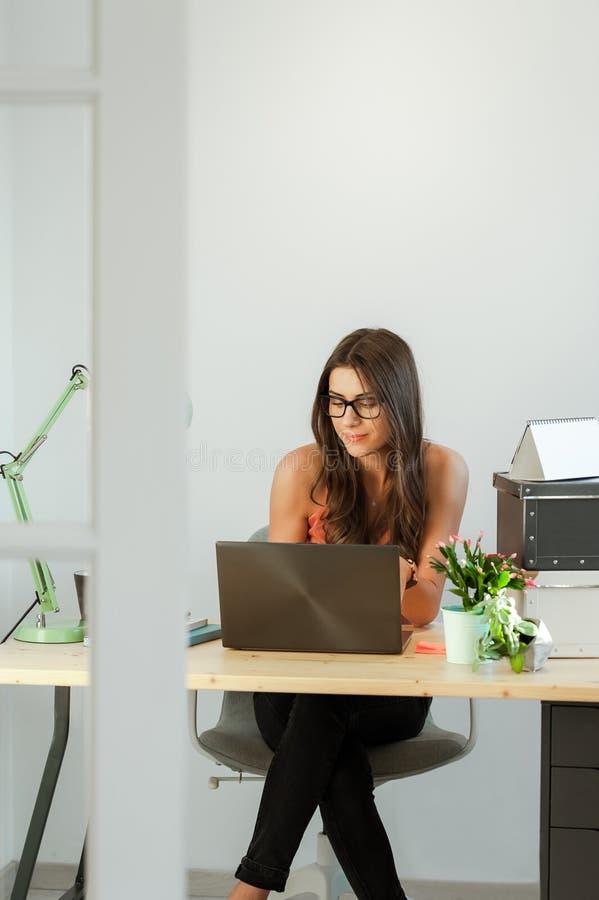 Het bureau van de vrouwenzitting thuis met laptop computer voor haar stock fotografie