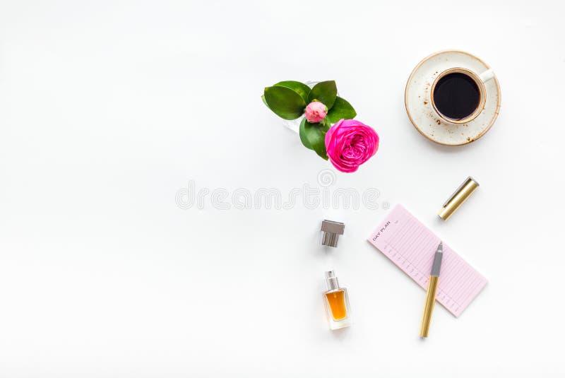 Het bureau van het huiswerk, vrouwelijke werkplaats Notitieboekje en kantoorbehoeften dichtbij roze bloemen en koffie op witte ho stock fotografie