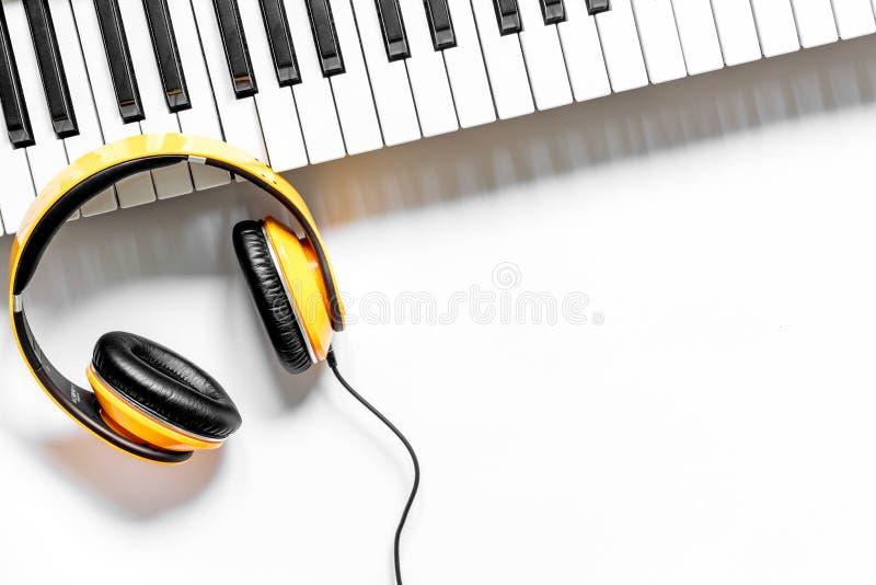 Het bureau van musicus voor songwriter het werk plaatste met hoofdtelefoons en synthesizer wit achtergrond hoogste meningsmodel stock foto's