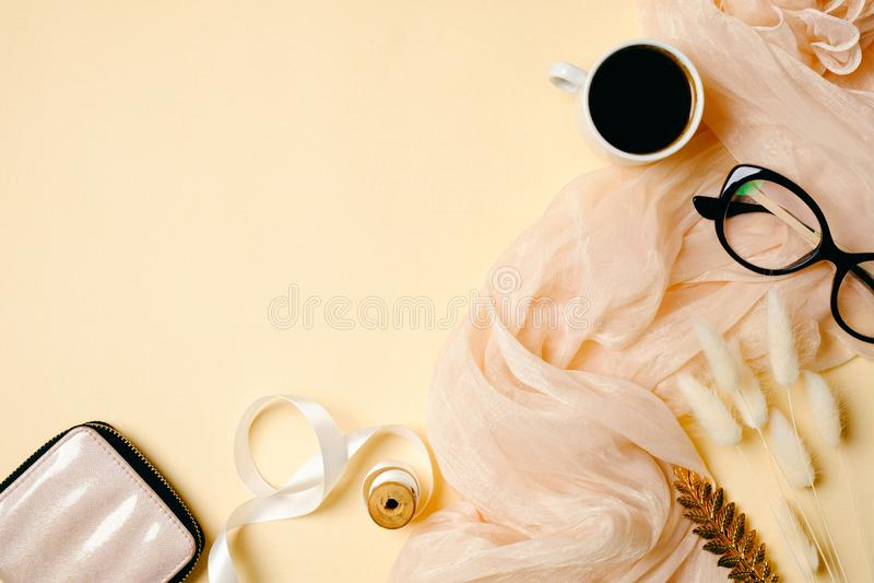 Het bureau van het vrouwenhuis met koffiekop, glazen, zijdesjaal en toebehoren op beige achtergrond Vlak leg schoonheids blogger  stock afbeelding