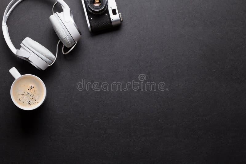 Het bureaulijst van het bureauleer met hoofdtelefoons, camera en koffie stock foto's
