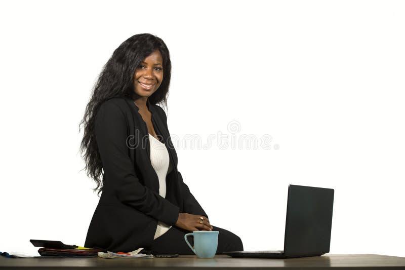 Het bureauportret van de jonge gelukkige en aantrekkelijke zwarte zitting van de afro Amerikaanse onderneemster elegant op bureau stock foto