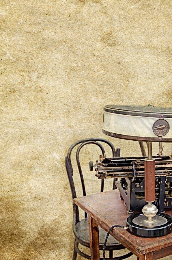 Het bureaustoel van de schemerlampschrijfmachine op de oude uitstekende geweven document achtergrond royalty-vrije stock fotografie