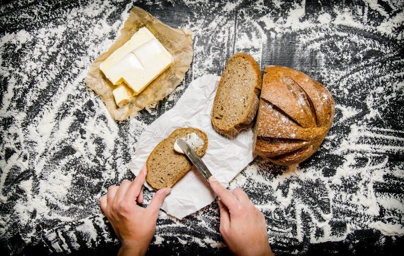 Het buttering van brood met boter aan boord met bloem stock afbeeldingen
