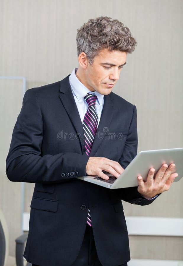 Het Call centre van zakenmanusing laptop at stock afbeeldingen