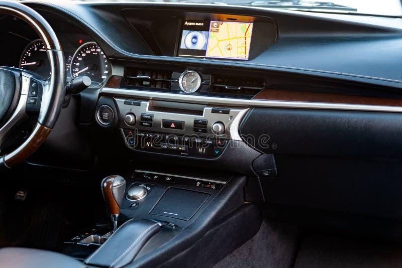 Het centrale consolepaneel binnen een zwarte auto met houten en chroomdelen, navigator en controleknopen, sensoren, versnellingsh royalty-vrije stock afbeelding