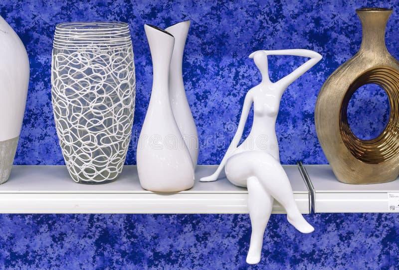 Het ceramische beeldje van vrouwen op een plank met vazen stock foto