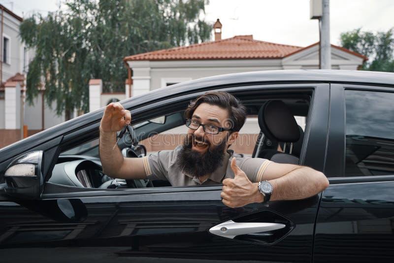 Het charismatische de autosleutels van de mensenholding tonen beduimelt omhoog royalty-vrije stock afbeelding