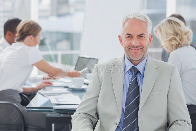 Het charismatische zakenman stellen in de bestuurskamer stock foto