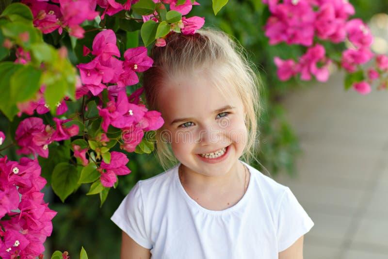 Het charmante blonde meisje lachen op de achtergrond van roze bloemen i stock foto