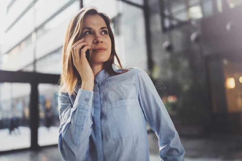 Het charmante jonge bedrijfsvrouw spreken met partner via mobiele telefoon terwijl status op modern commercieel centrum royalty-vrije stock foto