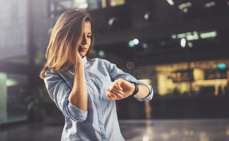 Het charmante jonge bedrijfsvrouw spreken met partner via mobiele telefoon terwijl status op modern commercieel centrum stock afbeelding