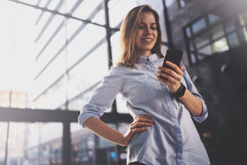 Het charmante jonge bedrijfsvrouw spreken met partner via mobiele telefoon terwijl status op modern commercieel centrum stock foto