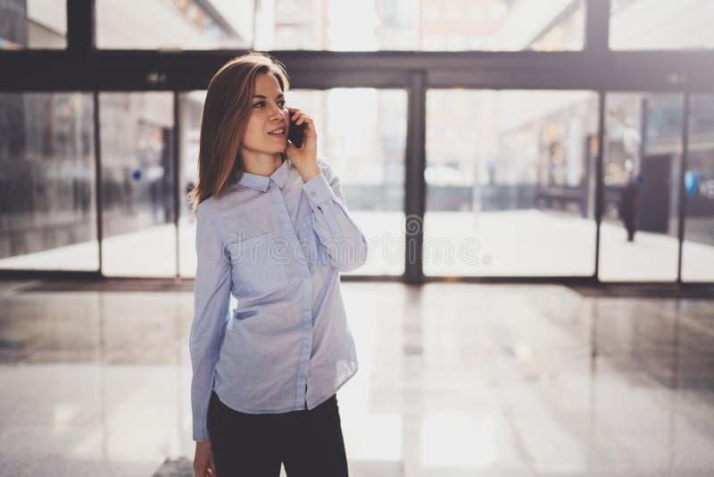 Het charmante jonge bedrijfsvrouw spreken met partner via mobiele telefoon terwijl status op modern commercieel centrum royalty-vrije stock foto's