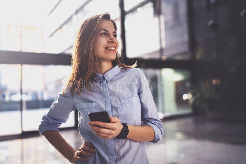 Het charmante jonge bedrijfsvrouw spreken met partner via mobiele telefoon terwijl status op modern commercieel centrum stock afbeeldingen